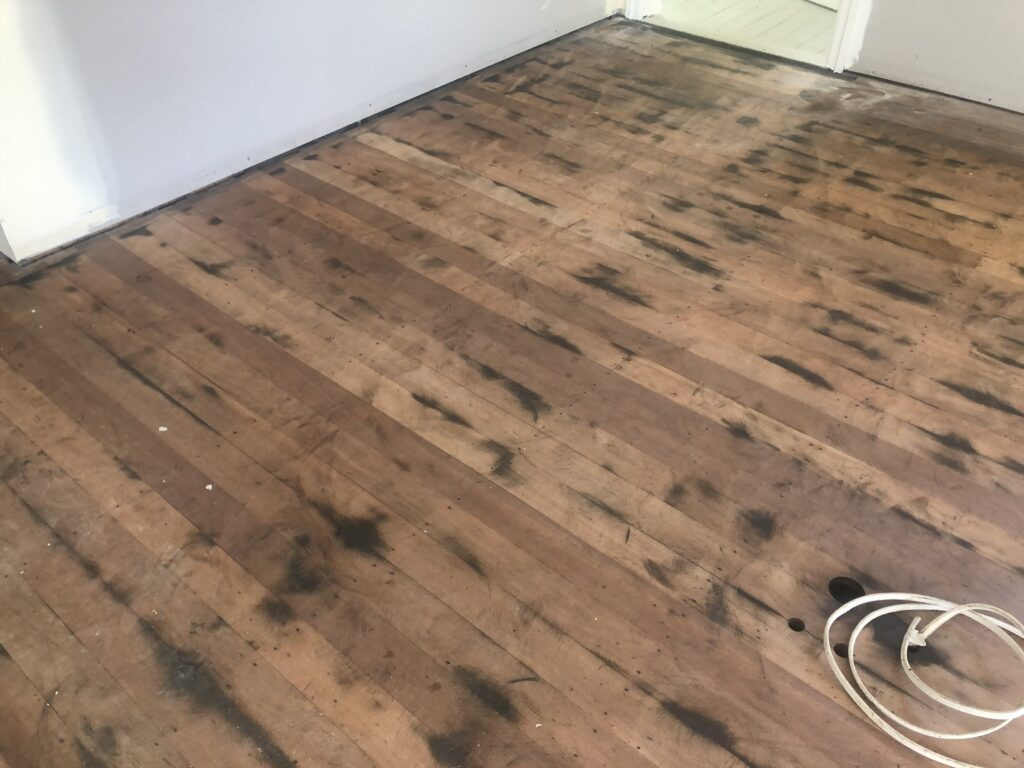 Before Rough sanded floor sanding off 80 year old black japan in Clayfield Non-Toxic Floors Australia