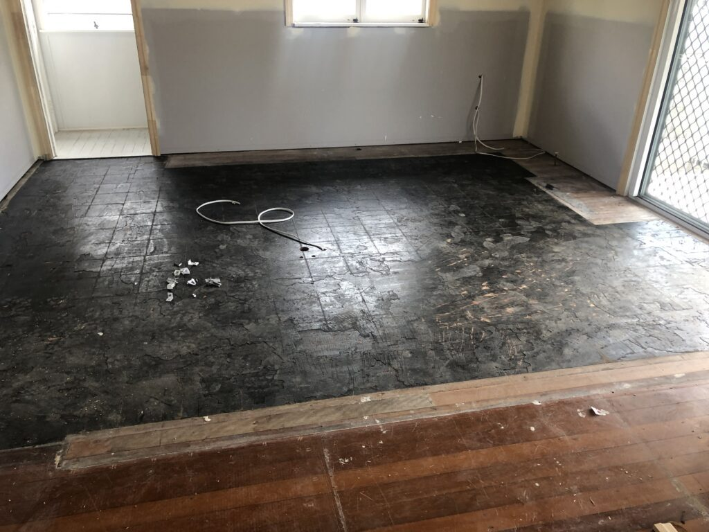 Before floor sanding off 80 year old black Japan and black tar water proofing in Clayfield Non-Toxic Floors Australia